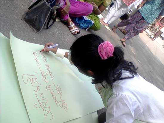 A student is writing placards against sexual harassment